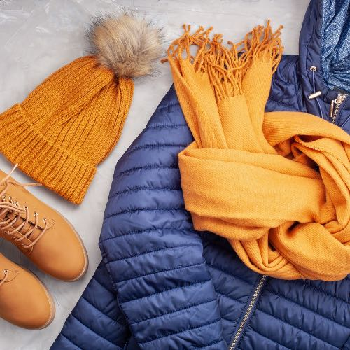 A blue puffer jacket and orange toque, scarf and boots