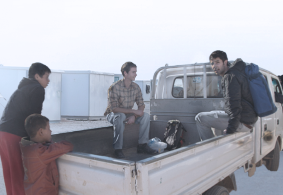A Film still from Salam Neighbor two men sitting in the back of a stationary pick up truck with two boys by the tail gate