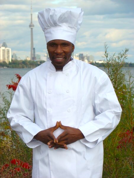Chef Peter, a black man in a white chefs uniform standing with Lake Ontario and the CN Tower behind him.